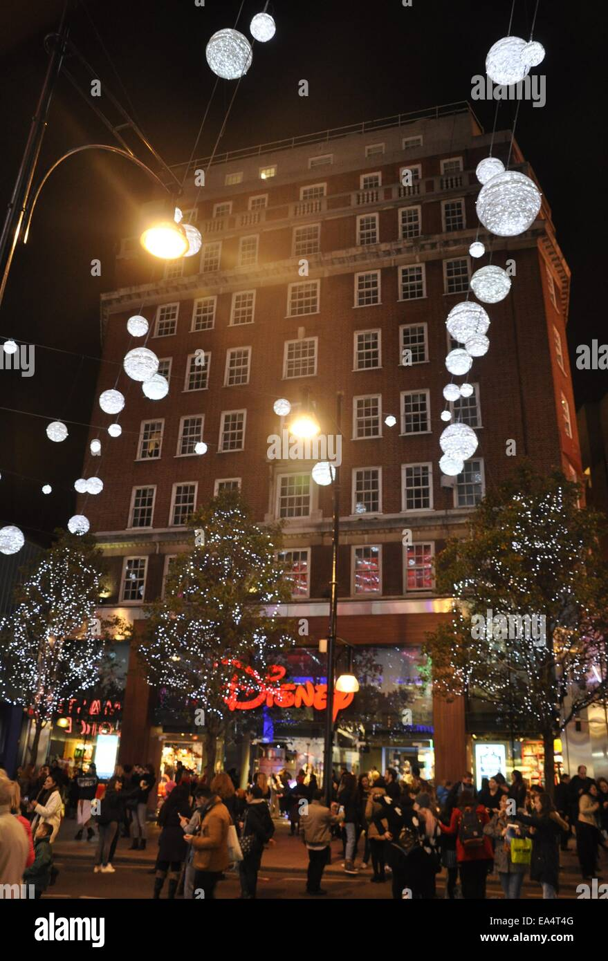 shoppers outside oxford street disney store with christmas lights at night time london - Christmas Lights Store