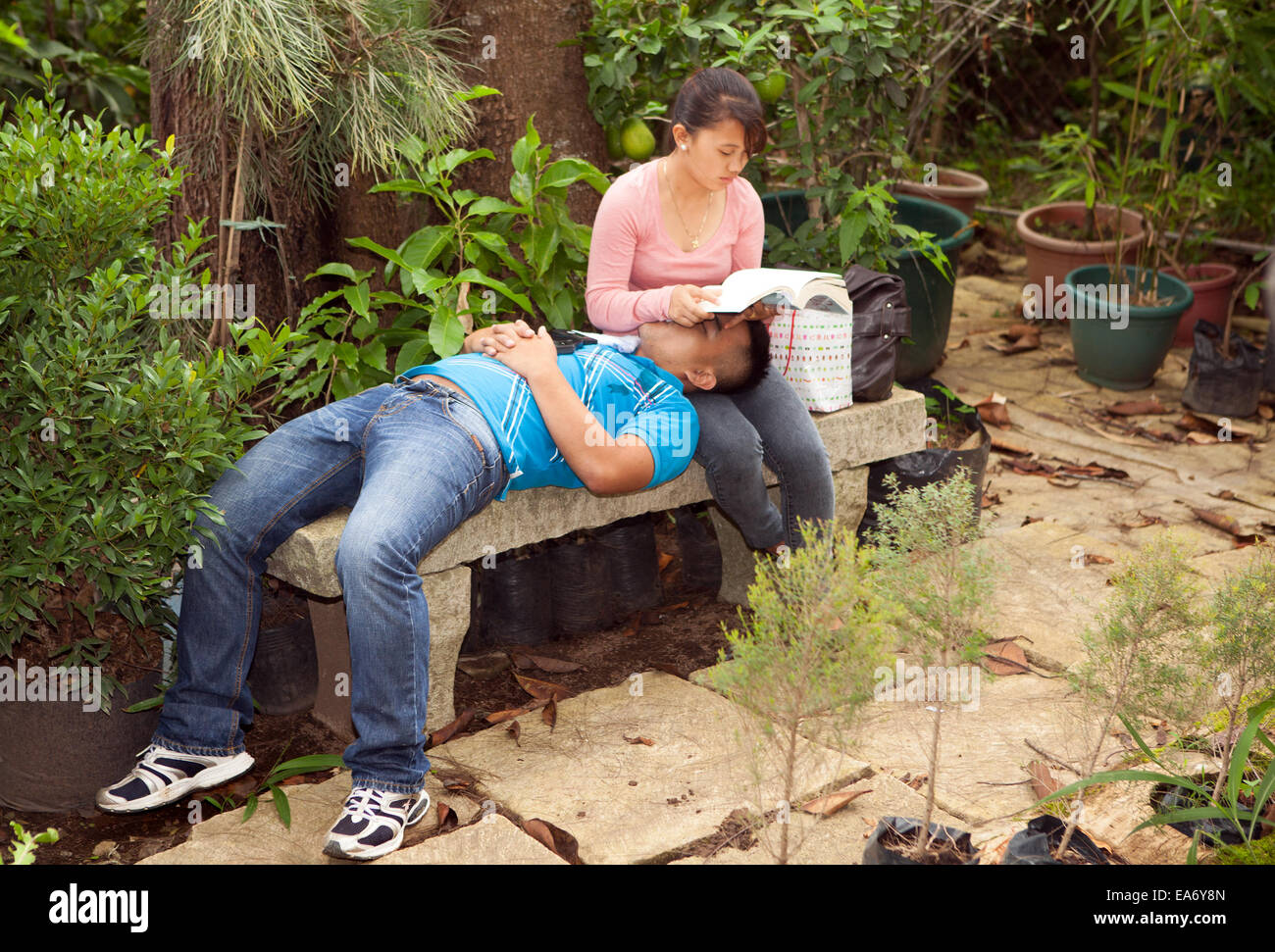Two Filipino Teenage College Students Sit Together In A Garden In ...