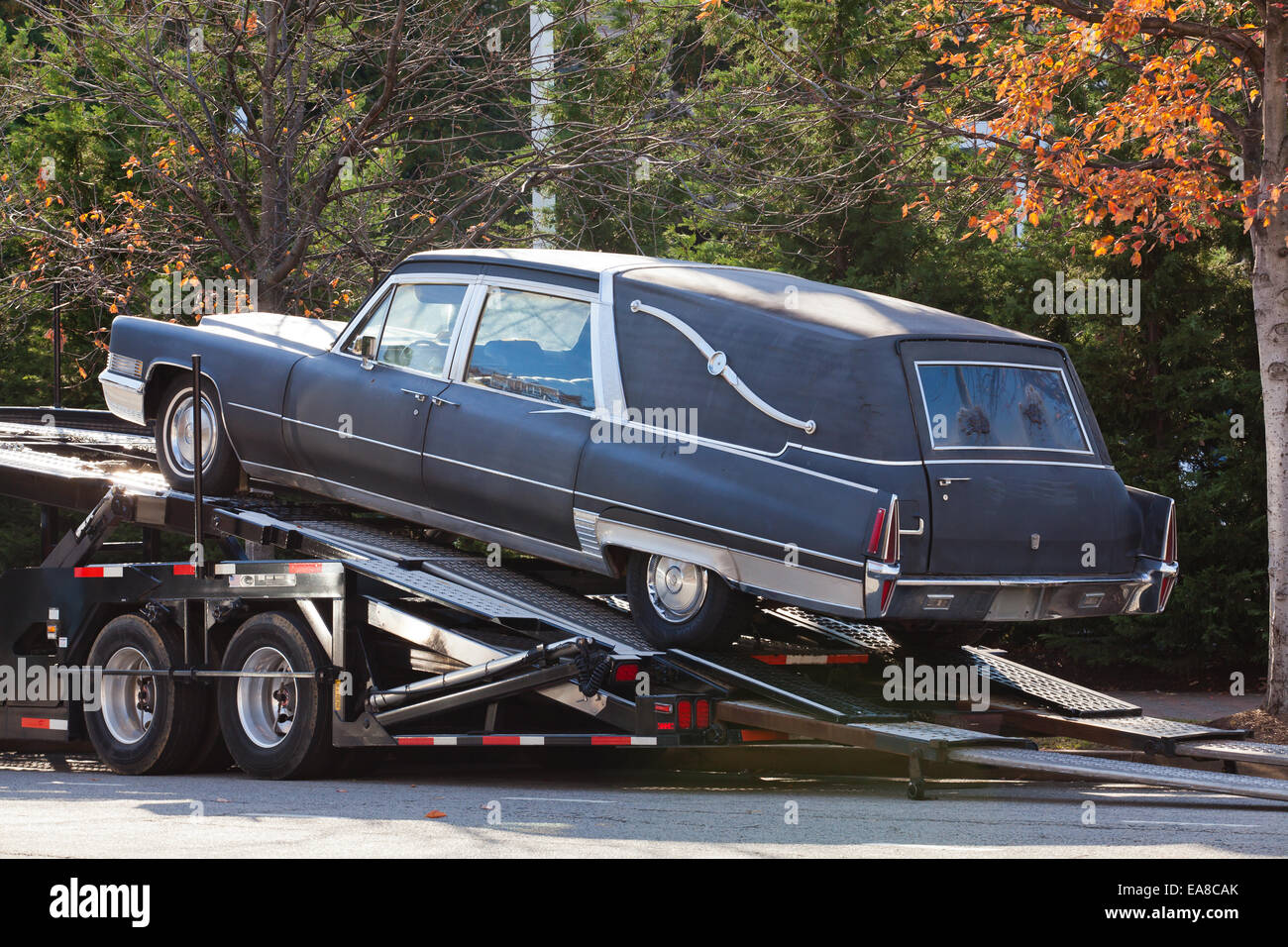 Old hearse on back of tow truck usa stock image