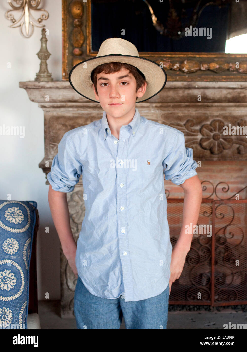 portrait of young boy wearing straw hat in mexican style room with