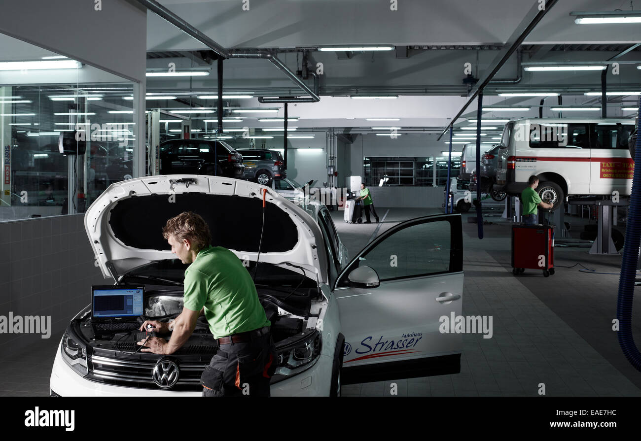 Car mechanic running fault diagnostics on a laptop, VW Strasser ...