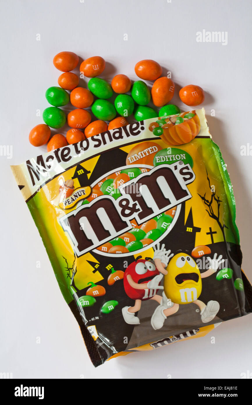 stock photo bag of limited edition peanut mms for halloween with contents spilled isolated on white background - Mms Halloween