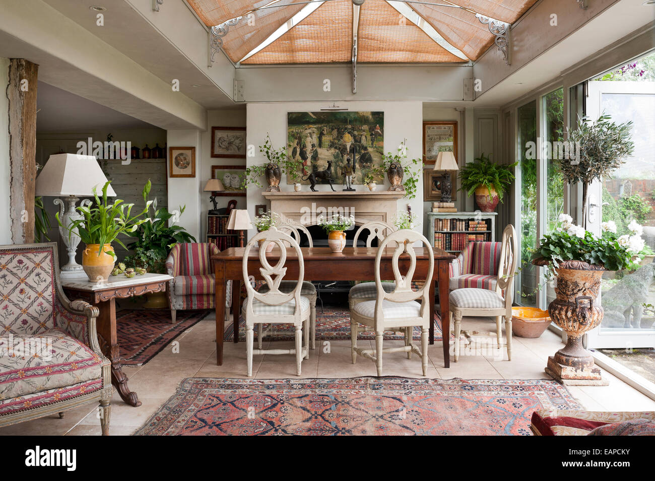 Roundback Wooden Dining Chairs Around Antique Farmhouse Table In Room With Persian Carpets And