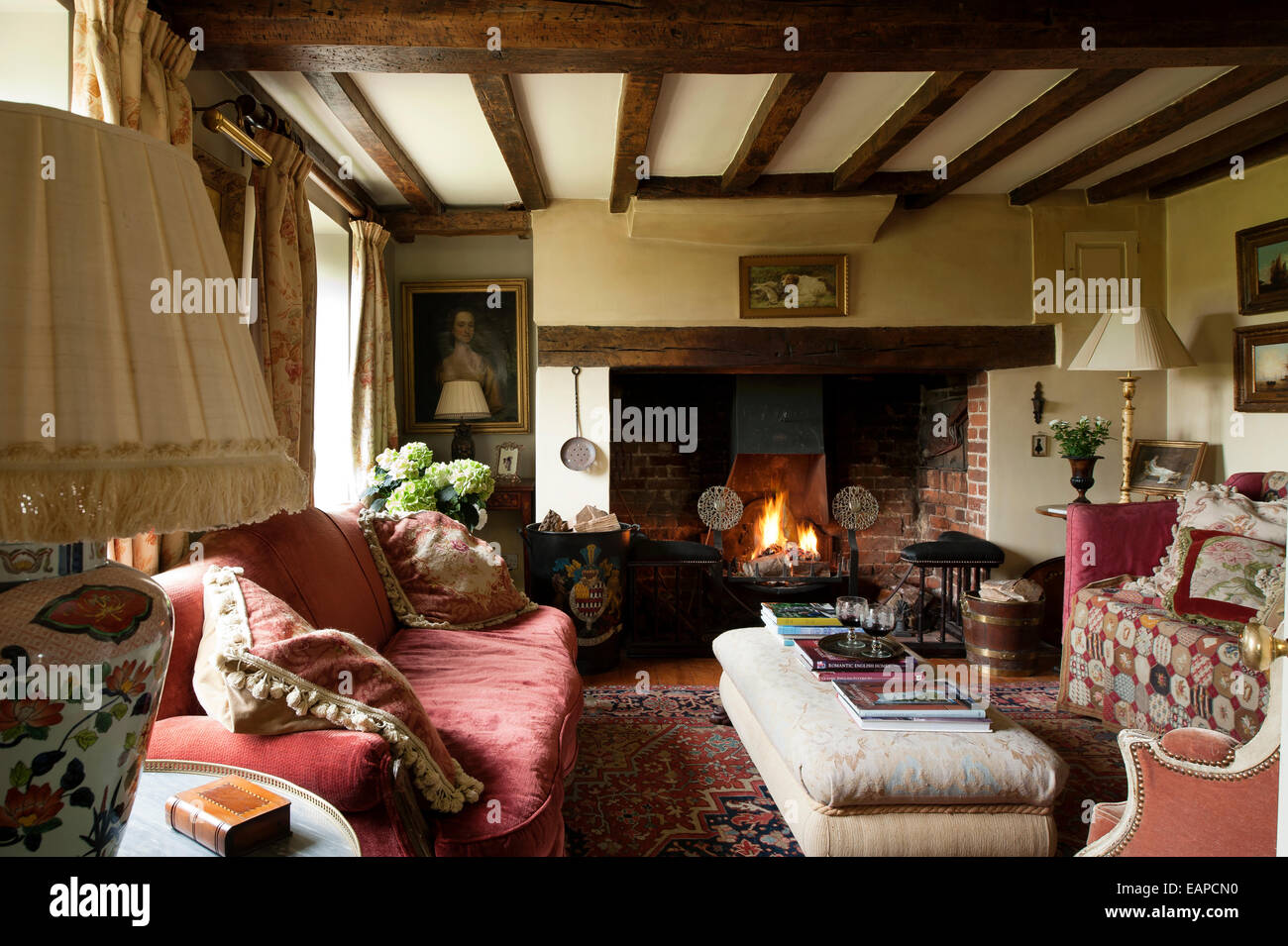 Inglenook Fireplace In Cosy Sitting Room With Original Beamed Ceiling And Red Sofa