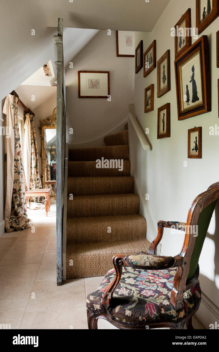 Antique Carved Tapestry Chair At Foot Of Staircase With Seagrass Carpet.  Antique Silhouette Pictures Adorn The Wall