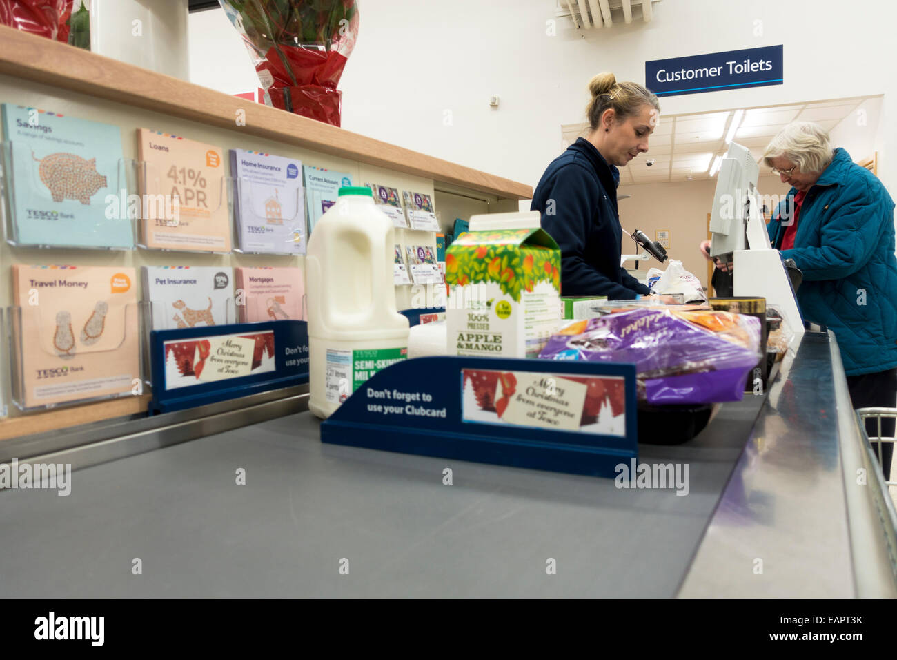 tesco checkout counter cashier handling customer shopping