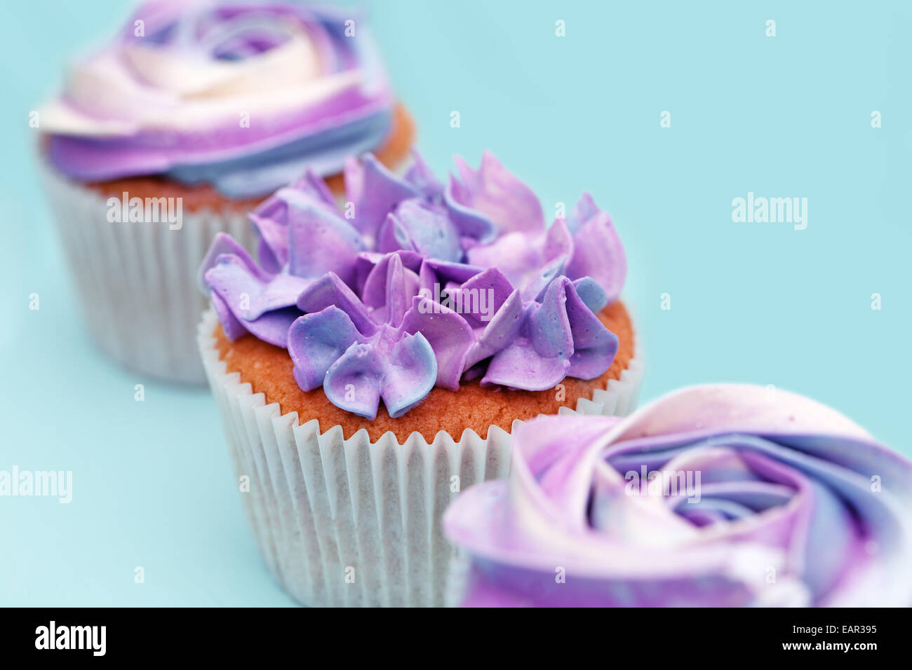 delicious sweet buffet with magenta cupcakes on cyan background