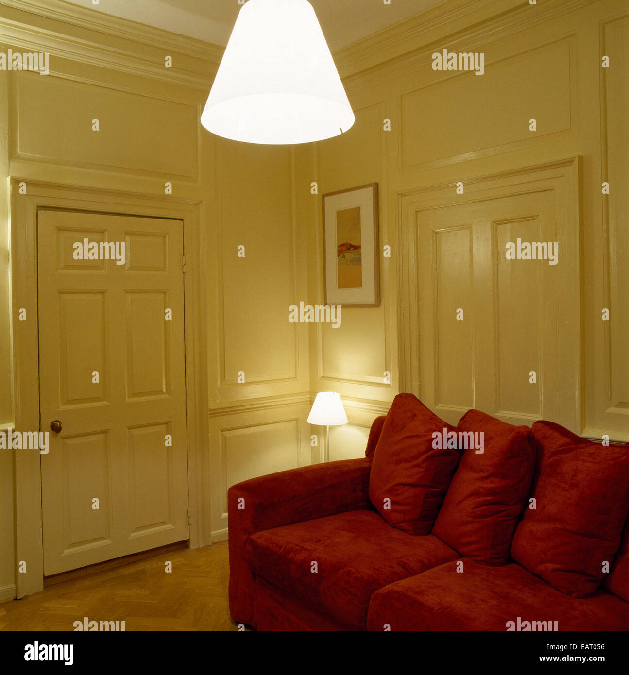 a traditional, yellow living room with wood panelled walls, red