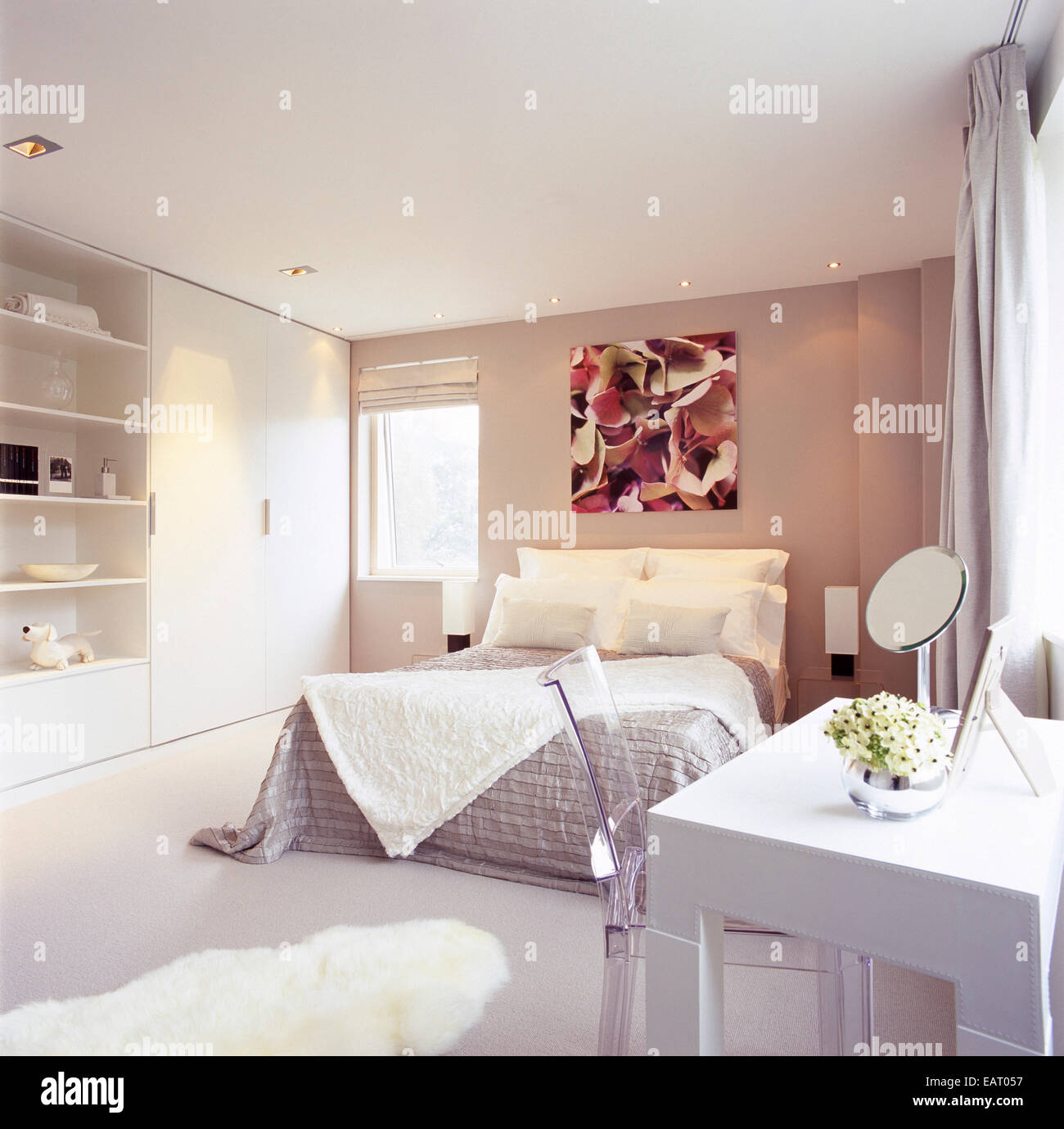 A modern bedroom with double bed, dressing table with a transparent perspex  chair, fitted wardrobe