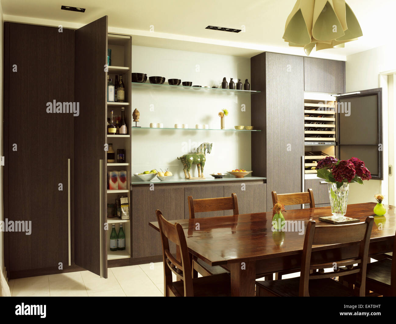 dining table and chairs in front of central island unit in spacious kitchen with wood units with open cupboard door spacious eat kitchen