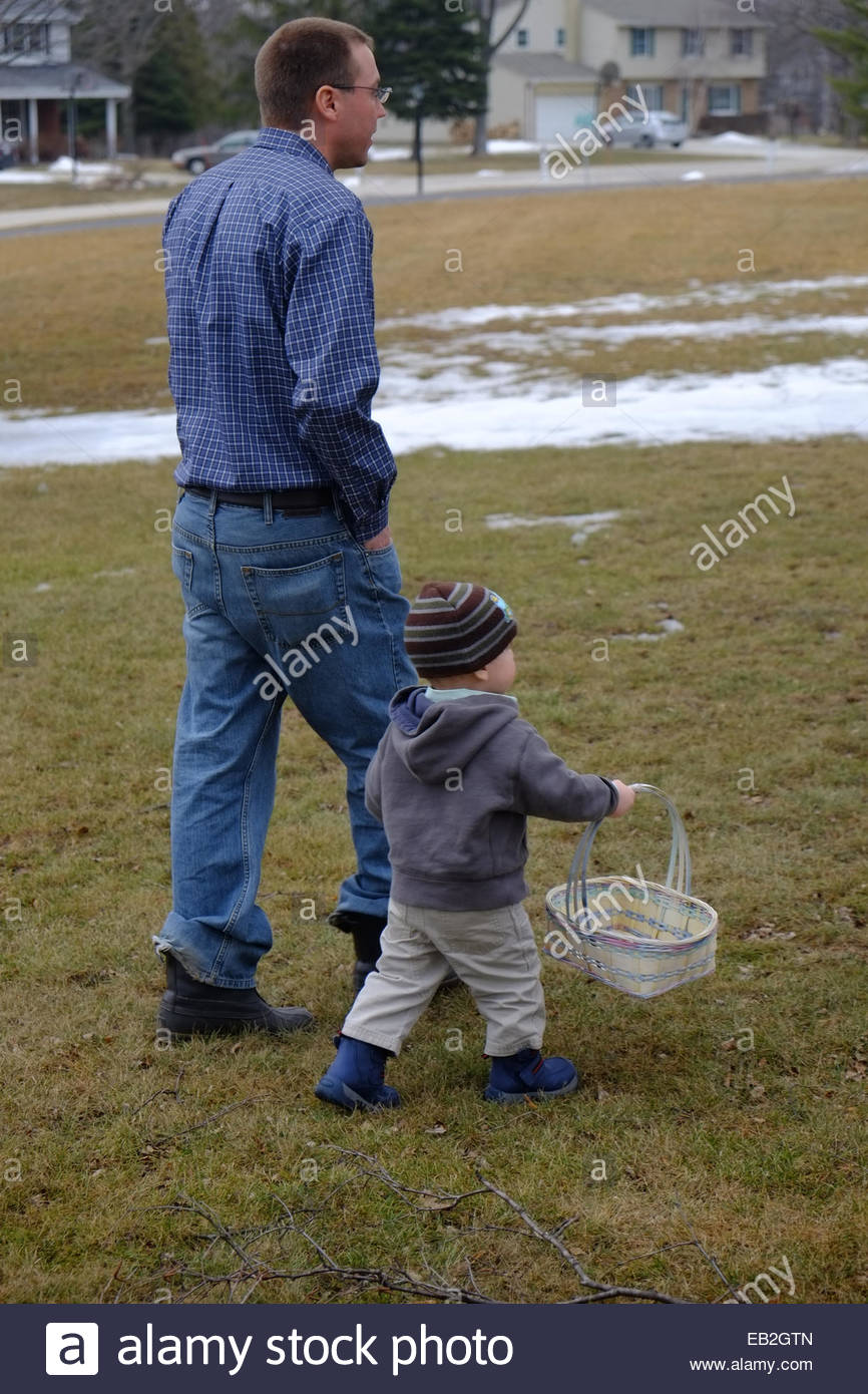 A young man walks with his son carrying an easter basket at a a young man walks with his son carrying an easter basket at a party in new berlin wisconsin negle Gallery