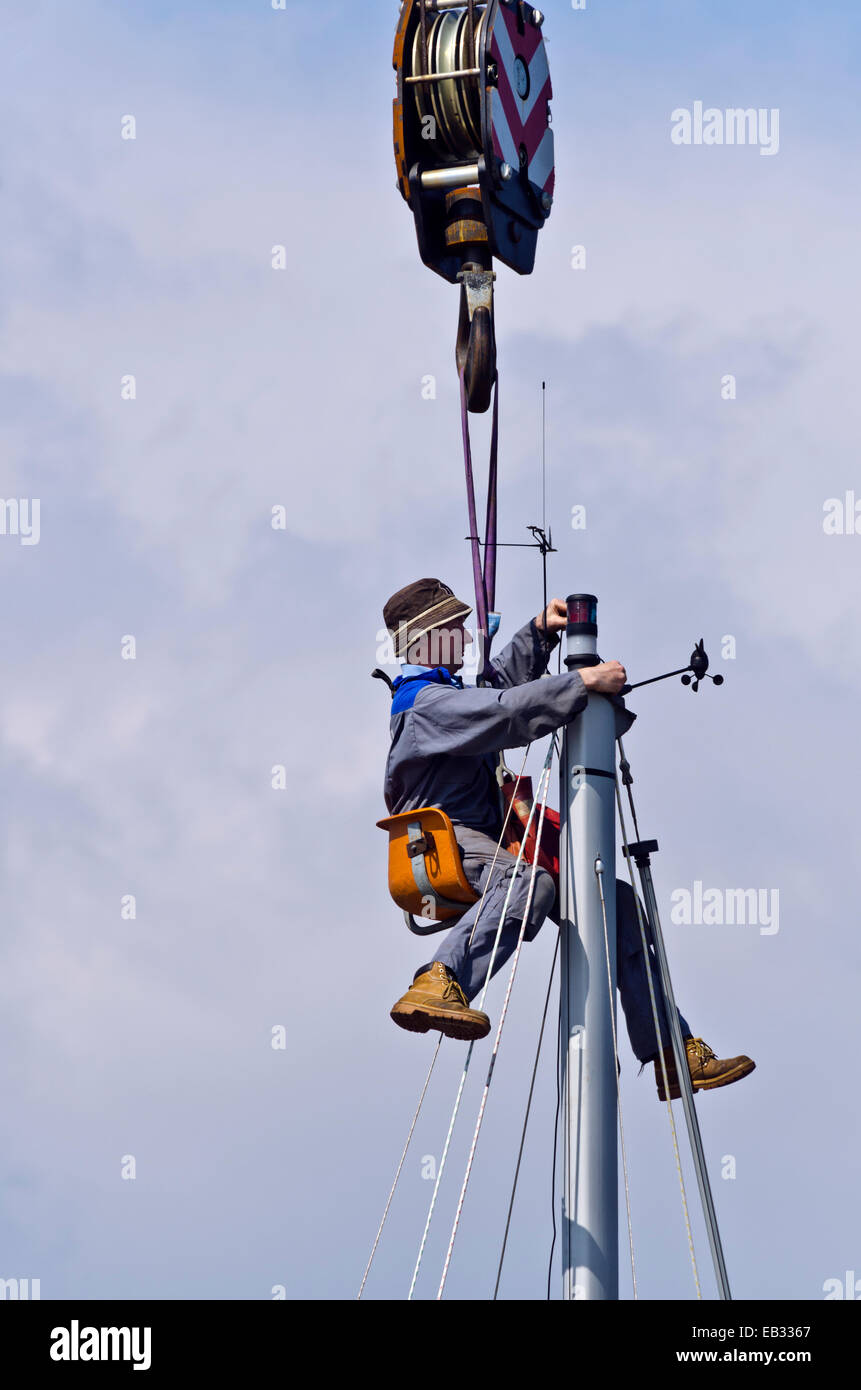 stock photo workman seated in bosunu0027s chair suspended from a crane working at the masthead of a yacht
