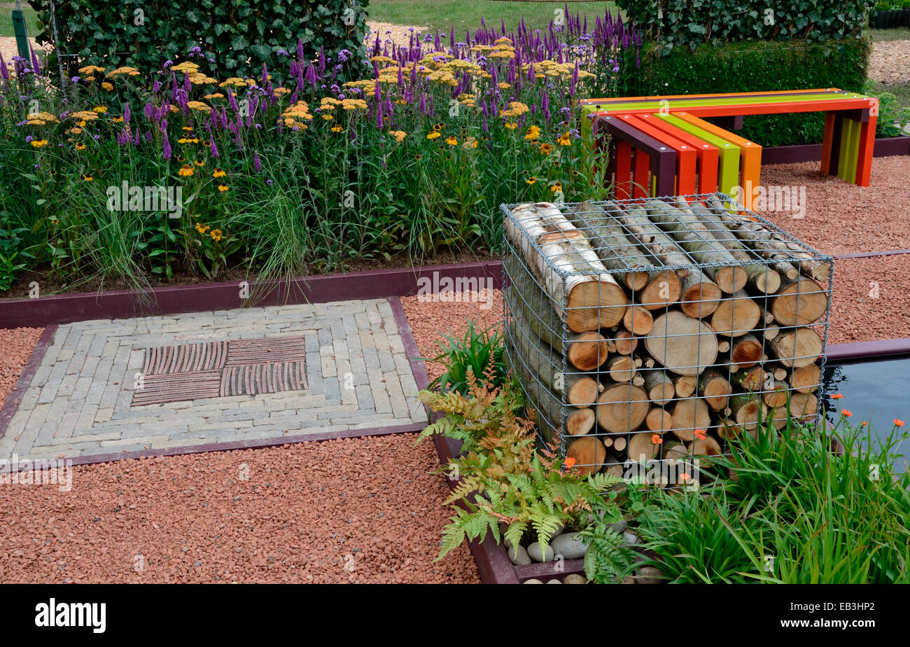 A Garden View With A Colourful Bench And A Cage Of Logs With A Decorative  Stone Insert In The Garden Path With Flower Border