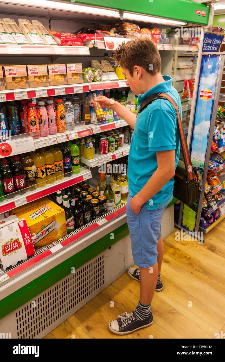 A 14 year old teenage boy choosing a soft drink in a Uk shop store. A 14 year old teenage boy choosing a soft drink in a Uk shop store