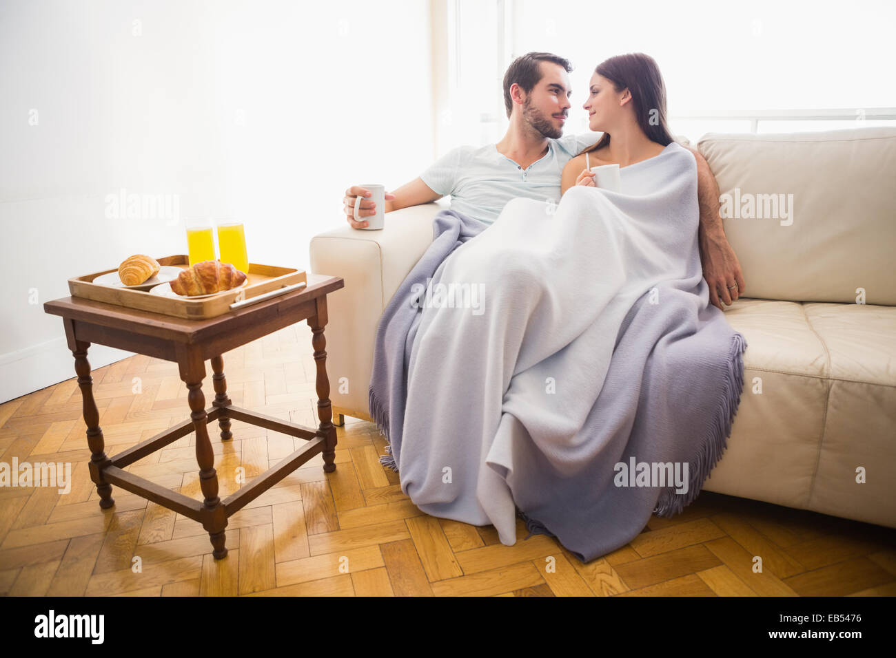 Cute couple relaxing on couch under blanket stock photo for Sofa kuscheln