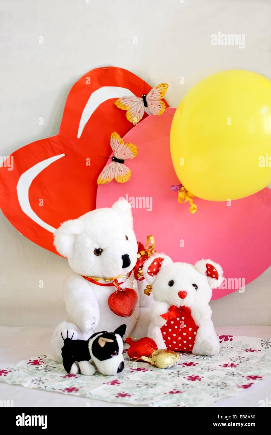Two Valentine Bears Sit On Printed Napkin With Two Paper Hearts As Backdrop  One Heart Is Pink And The Other Is Red They Have
