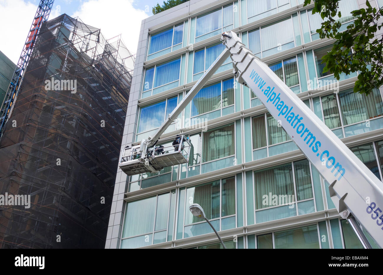 cherry picker being used for window cleaning of a modern