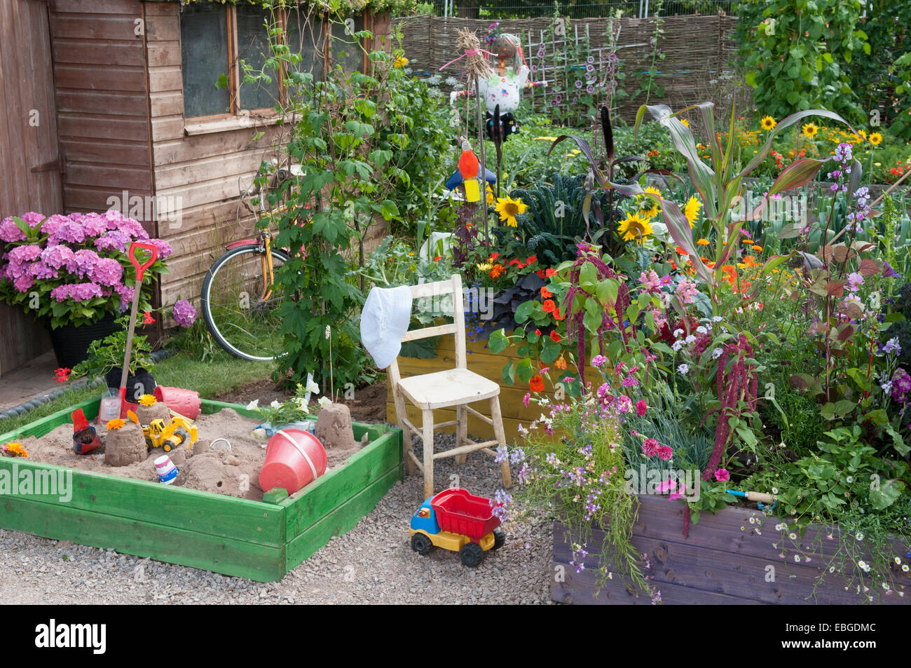 childrens play area in a busy garden of raised flower beds Stock ...