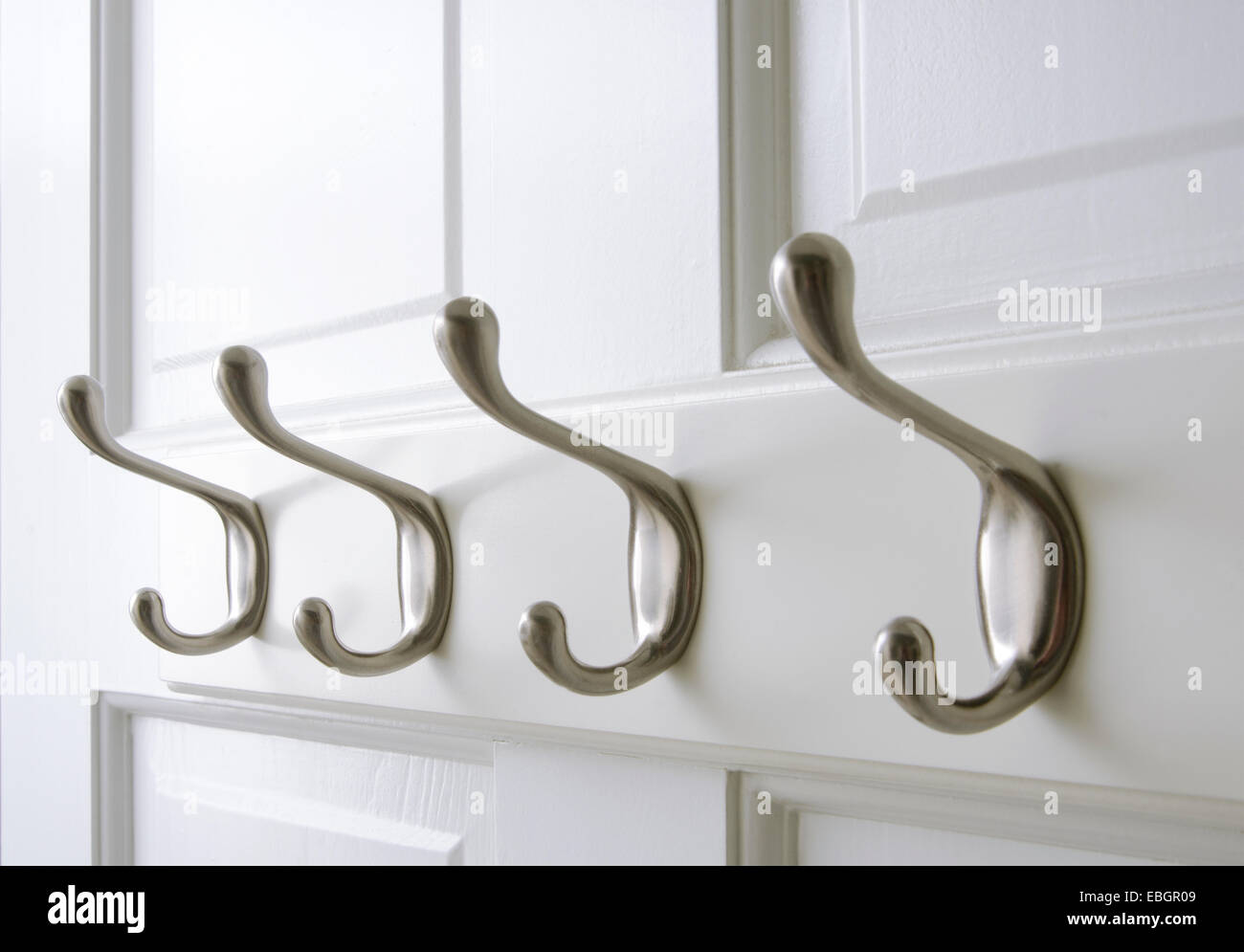Chrome coat hooks are mounted on the back of a closet door & Chrome coat hooks are mounted on the back of a closet door Stock ...