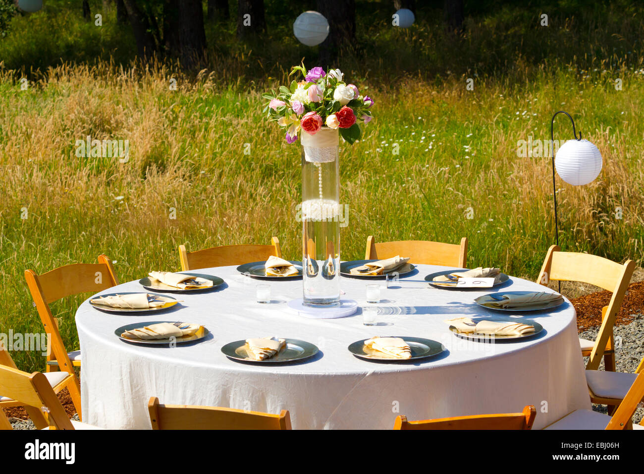 Dining Table At A Wedding Reception Outdoors With Plates And Silverware Ready For Eating