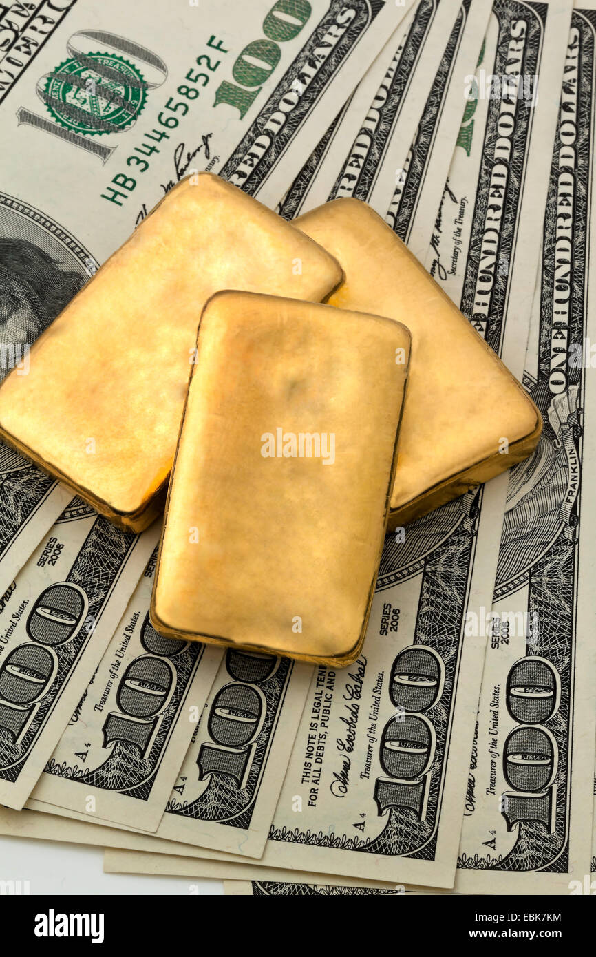 Gold bars on 100 dollar bills symbolising an investment in gold gold bars on 100 dollar bills symbolising an investment in gold biocorpaavc Images