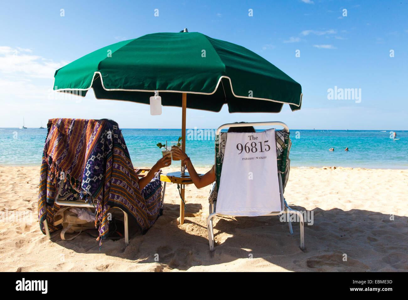 Two Woman Enjoying A Drink On The Beach Under Umbrella