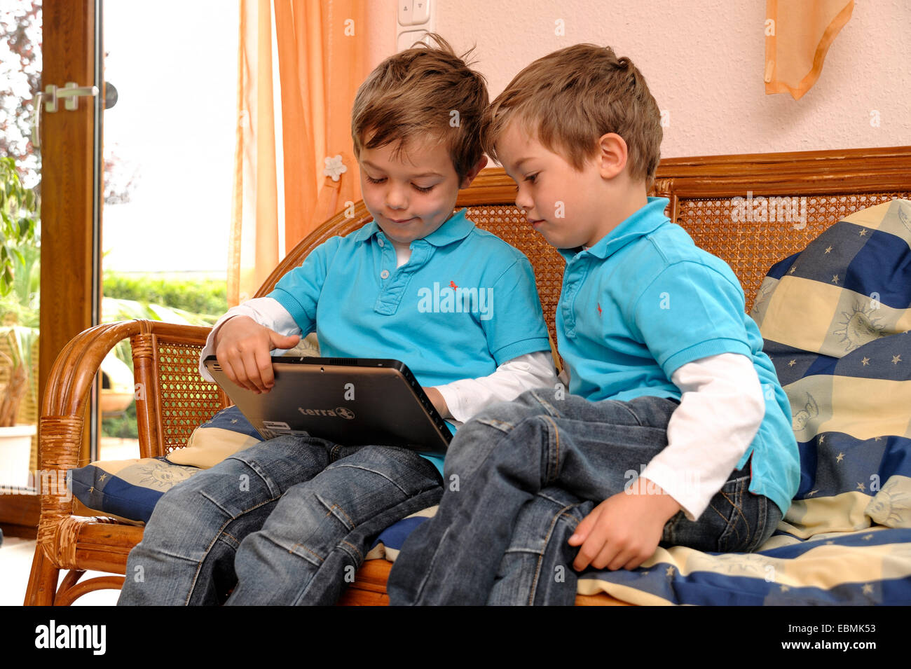 Two boys twins sitting side by side on a bench in a for 2 living rooms side by side