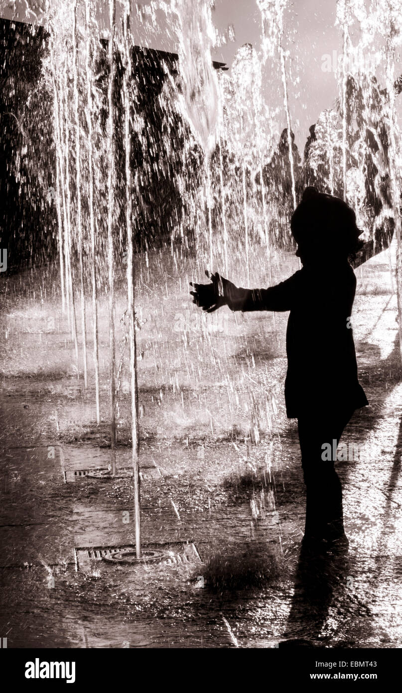 A Silhouette Of Little Girl Having Playing With Water Fountain