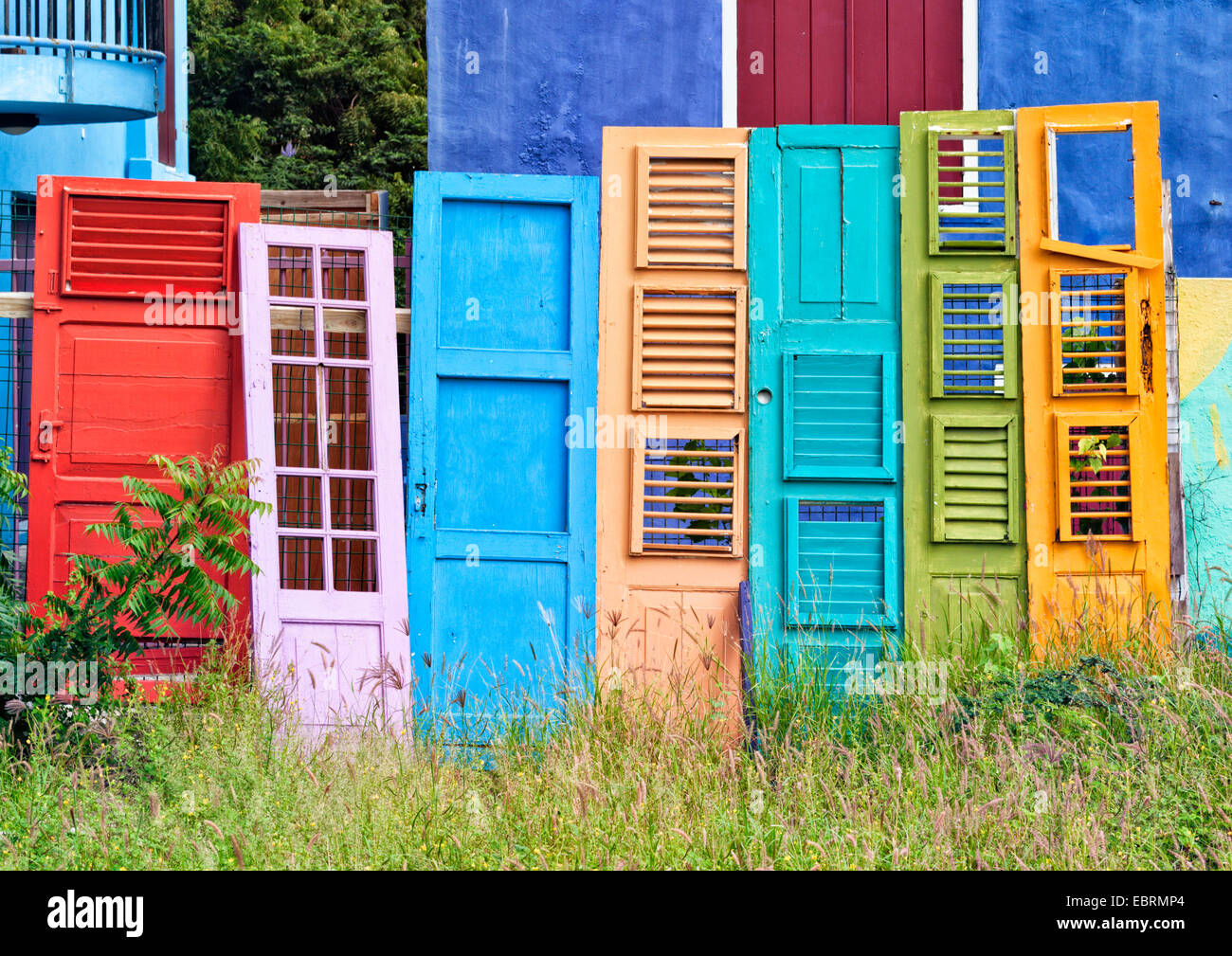 Collection of colorful old wooden doors and shutters leaning on ...