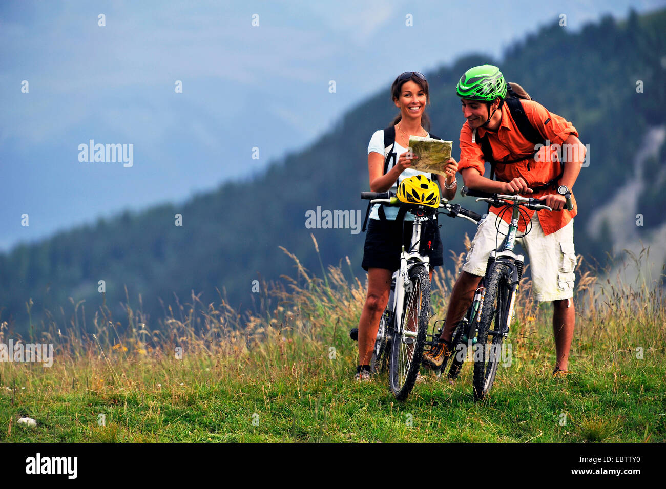 two mountain bikers looking on a trail map in the Alps France Stock