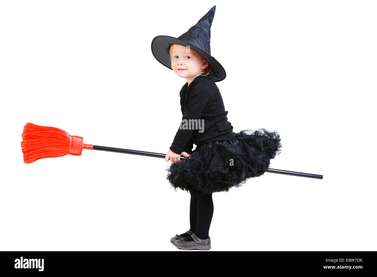 little girl in witch costume sitting back to front on a broom ...