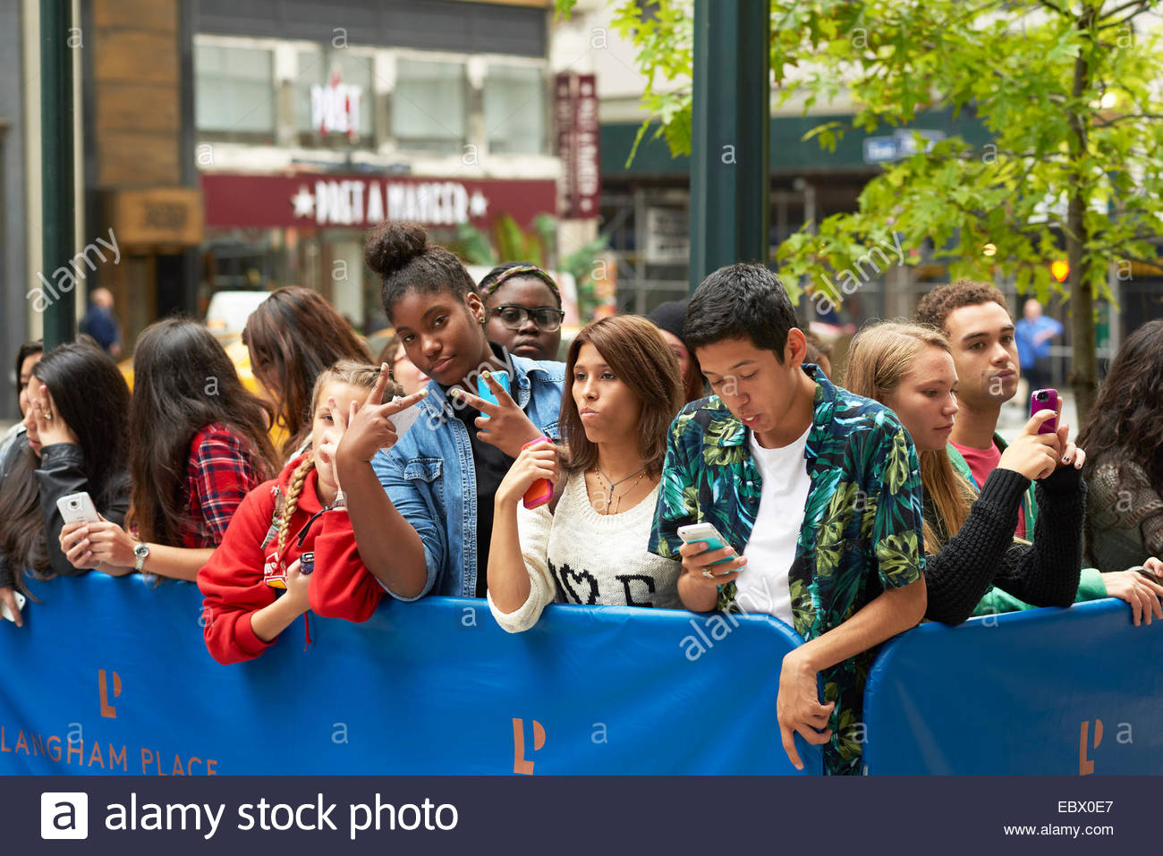 Fans taking pictures with cell phone behind barrier stock photo - Young Girl Fans Behind Barrier Chasing Pop Stars On The Streets Of Manhattan New York
