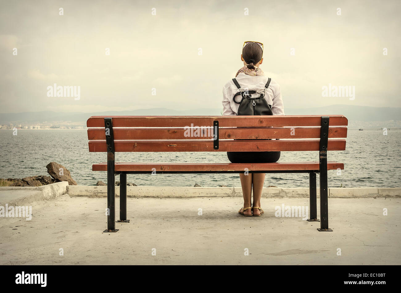 Lonely Woman Sitting On A Bench By The Sea Stock Photo Royalty Free Image 76239628 Alamy
