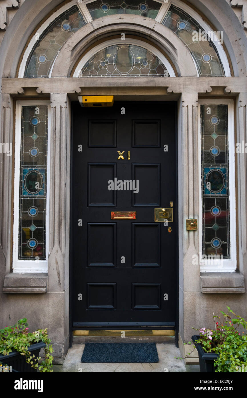 Black No XI front door with potted plants outside period house in city centre Edinburgh Scotland UK & Black No XI front door with potted plants outside period house in ...