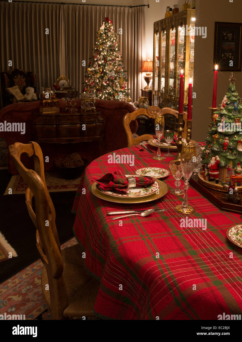 Christmas dinner table set with decorated Christmas tree in background