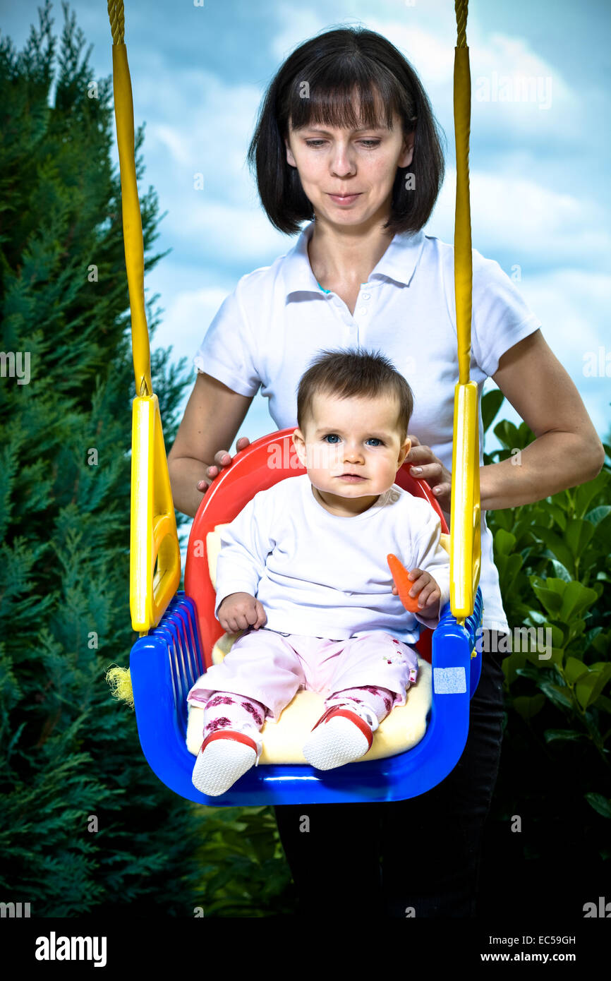 A 8 Month Old Girl Swinging With Mom In The Garden Stock Photo