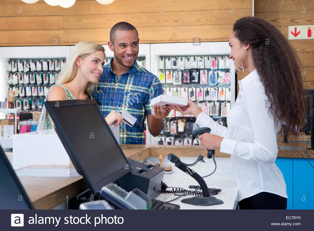 shop assistant and customer stock photos shop assistant and couple making a purchase from store assistant in shop stock image