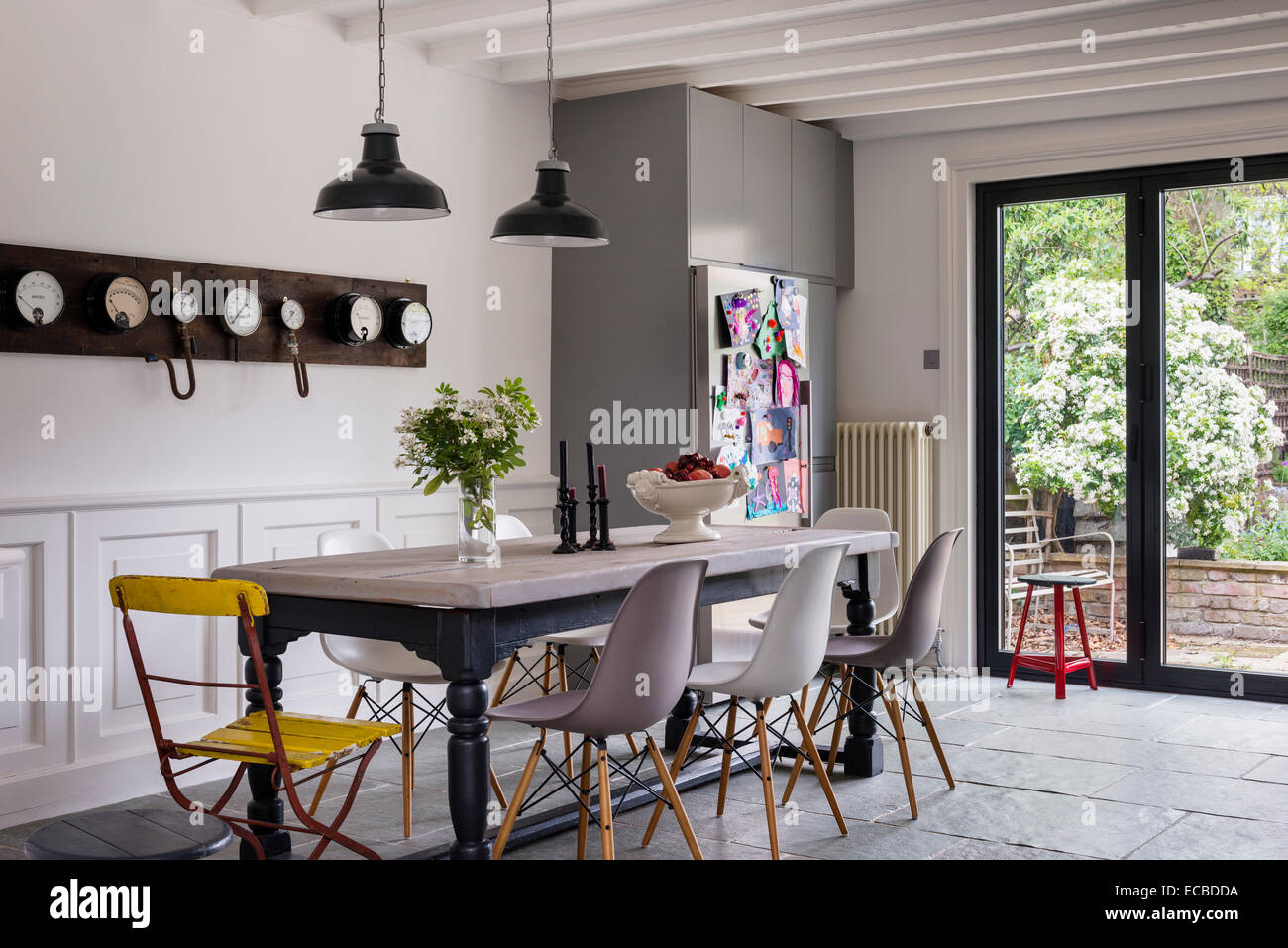 Eames DSW Chairs Around Farmhouse Table In Kitchen With Limestone Flooring  And Pendant Lights