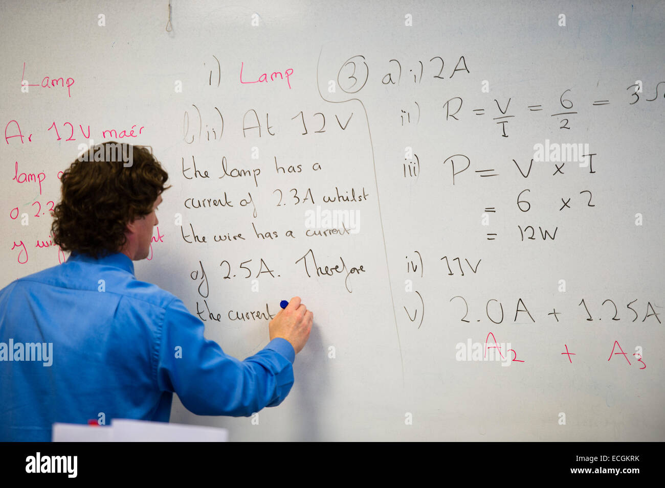 A male teacher writing equations (Ohm's Law and Watt's Law on ...