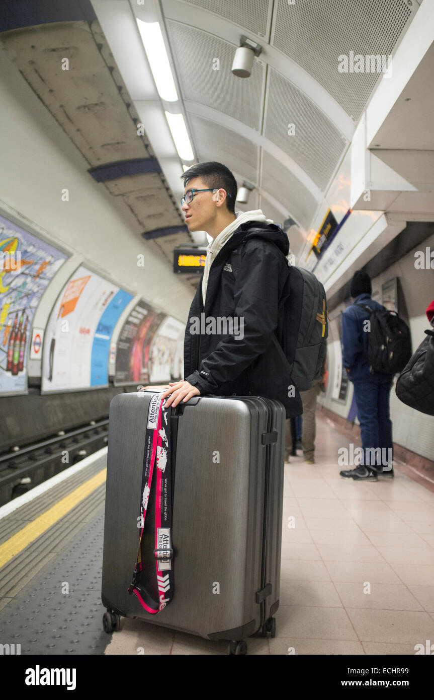 Asian tourist on London Underground platform with a very large ...