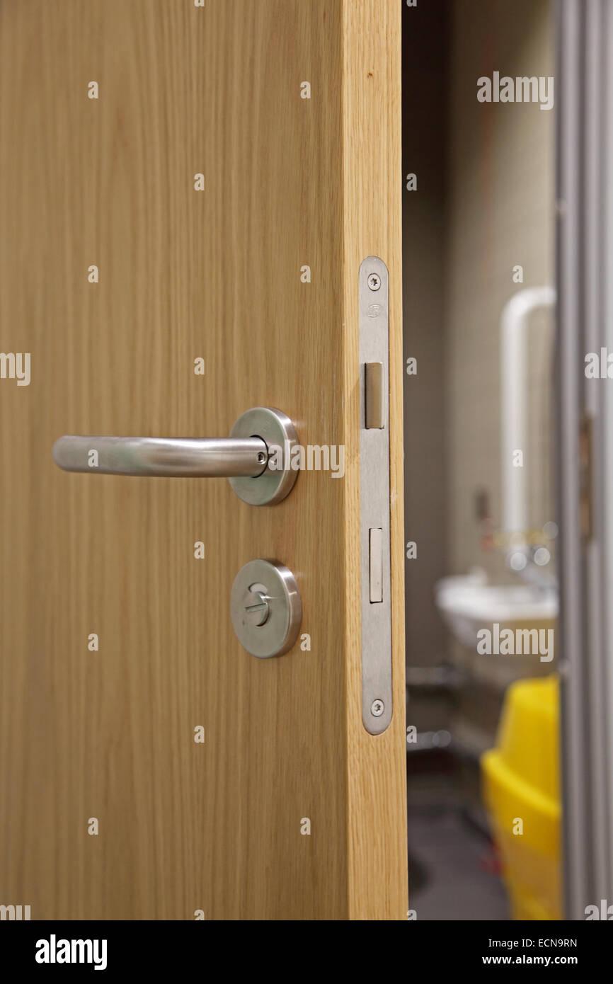 A Partially Open Modern Oak Finish Interior Door Showing