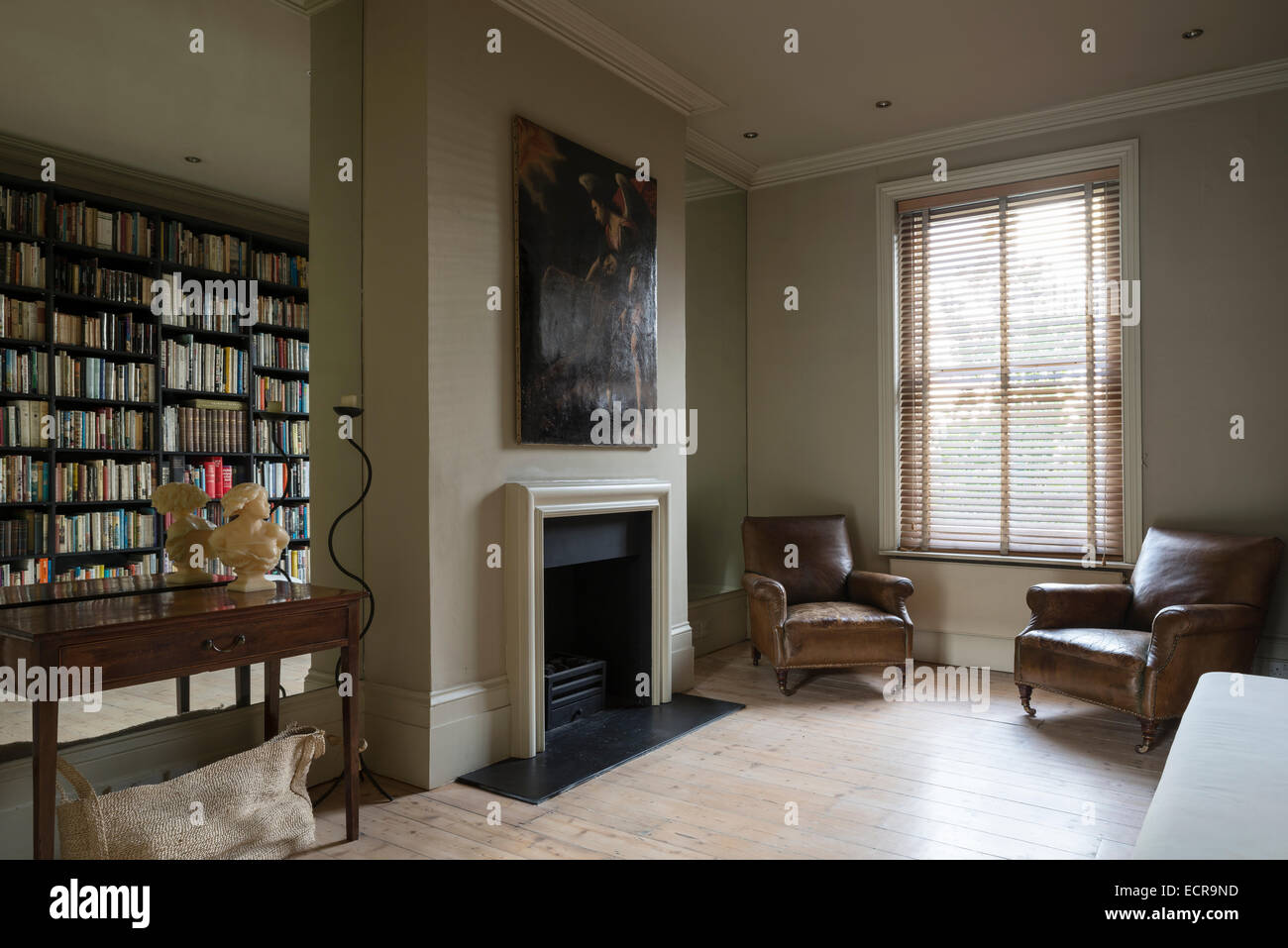 Oil painting above fireplace in minimal living room with old oil painting above fireplace in minimal living room with old leather chairs and mirrored walls amipublicfo Choice Image