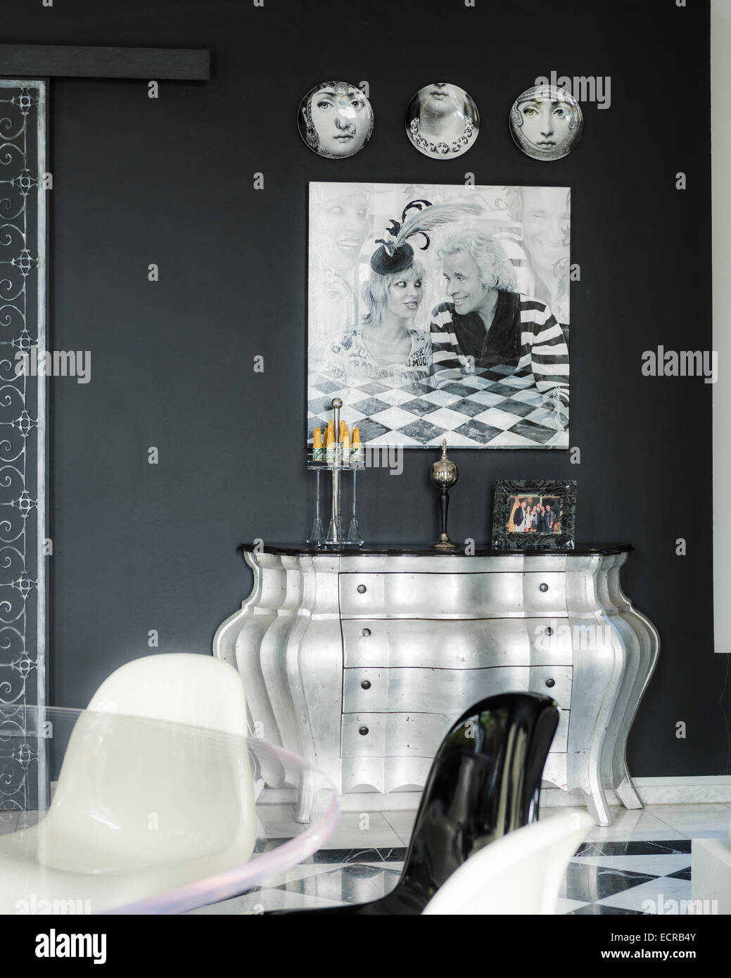 fornasetti plates on wall with painting above silver bombe style chest of drawers