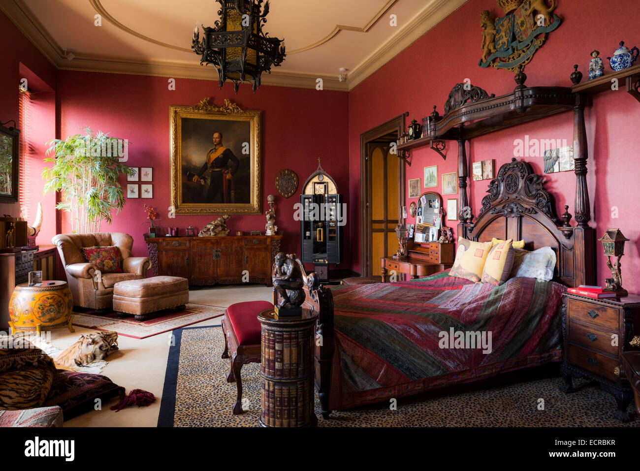 ornate carved bed with coronet in large red bedroom with leopard print carpet wall mounted coat of arms and antique furniture - Ornate Bedroom Furniture