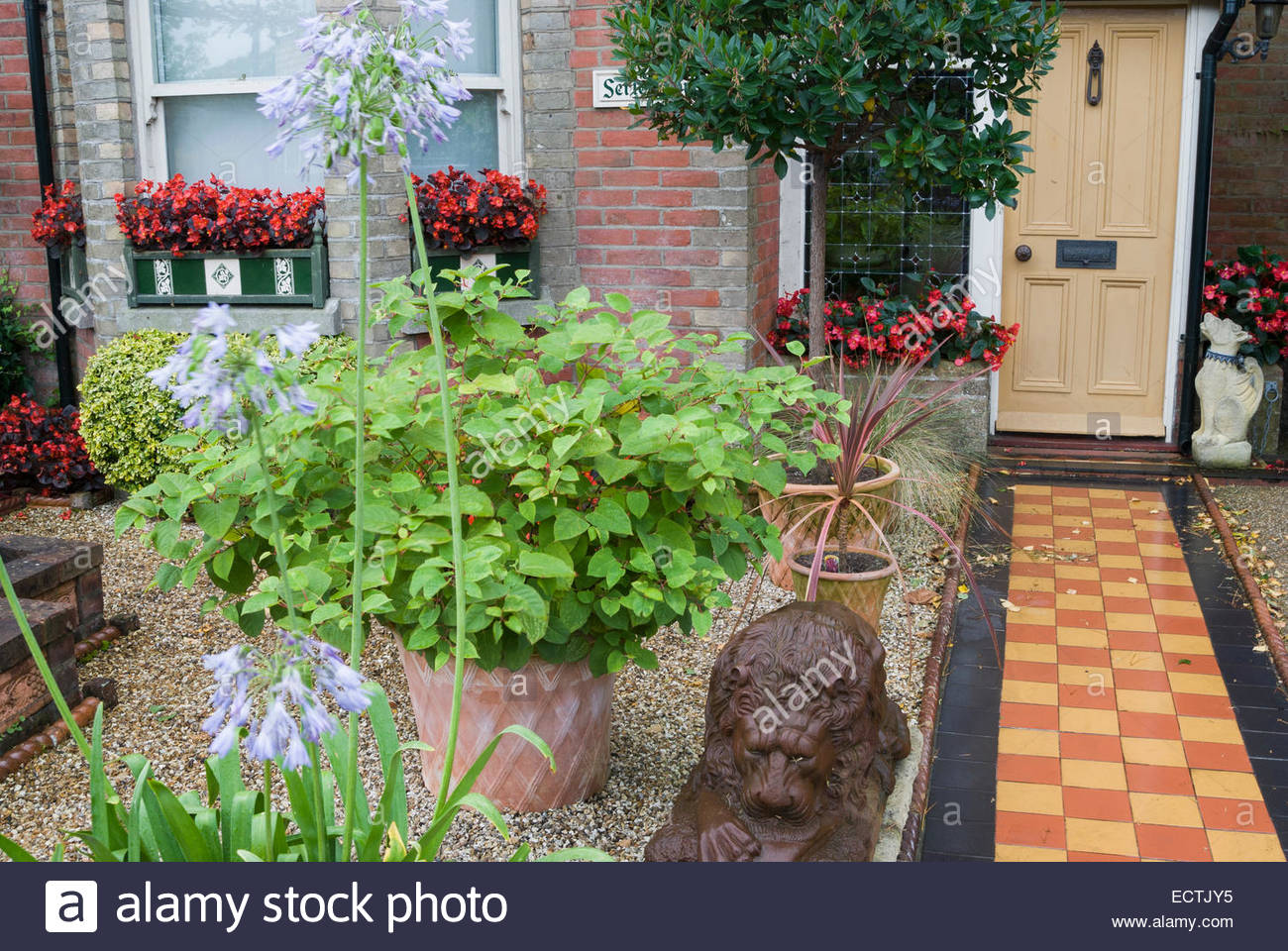 Front garden of victorian terraced house features a tiled for Victorian terraced house garden design