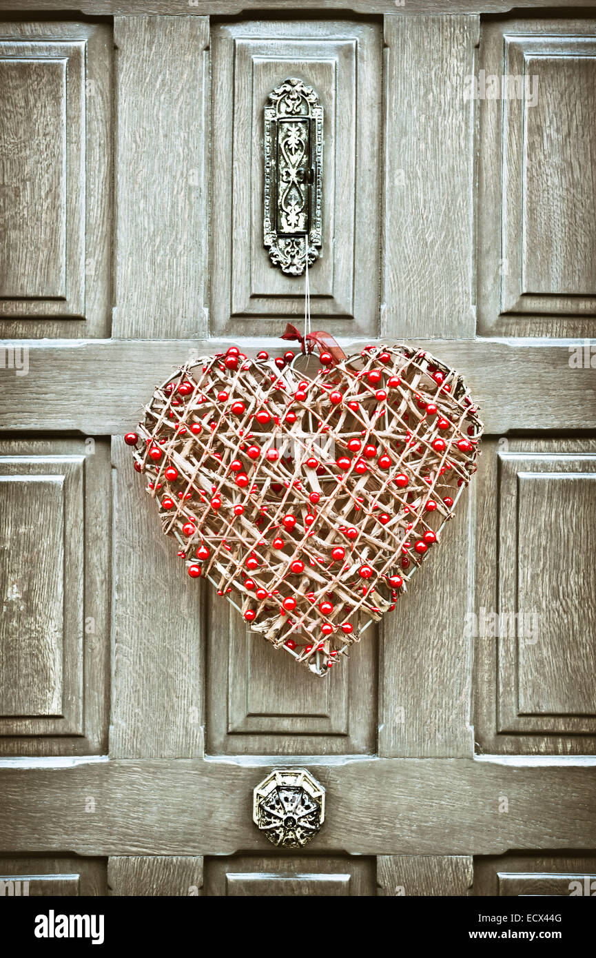 A heart shaped christmas wreath on a wooden front door stock photo a heart shaped christmas wreath on a wooden front door rubansaba