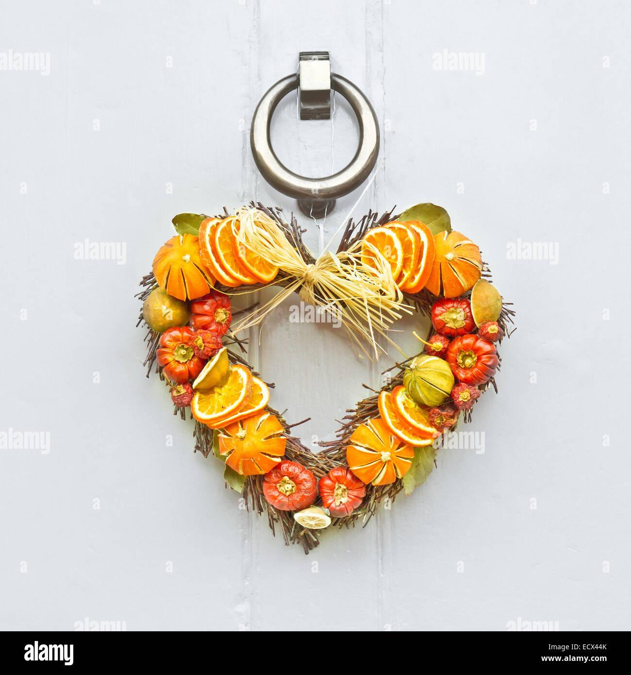 A heart shaped fruit christmas wreath on a wooden front door stock a heart shaped fruit christmas wreath on a wooden front door rubansaba