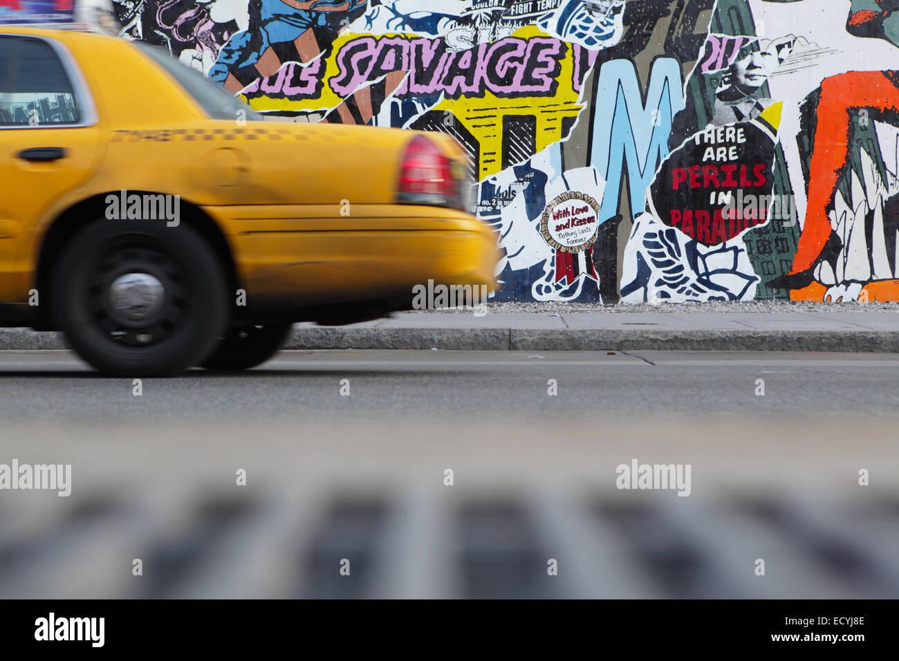 A Yellow New York City Taxi Cab Drives East Past The Bowery Mural Wall On  The Bowery And Houston Street NYC