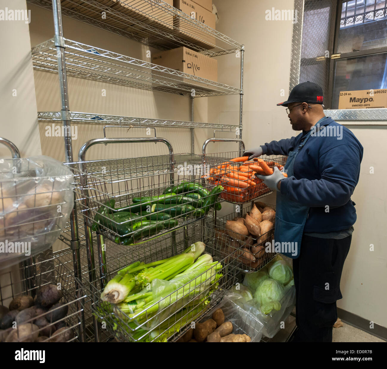 A volunteer stocks vegetables at the West Side Campaign Against