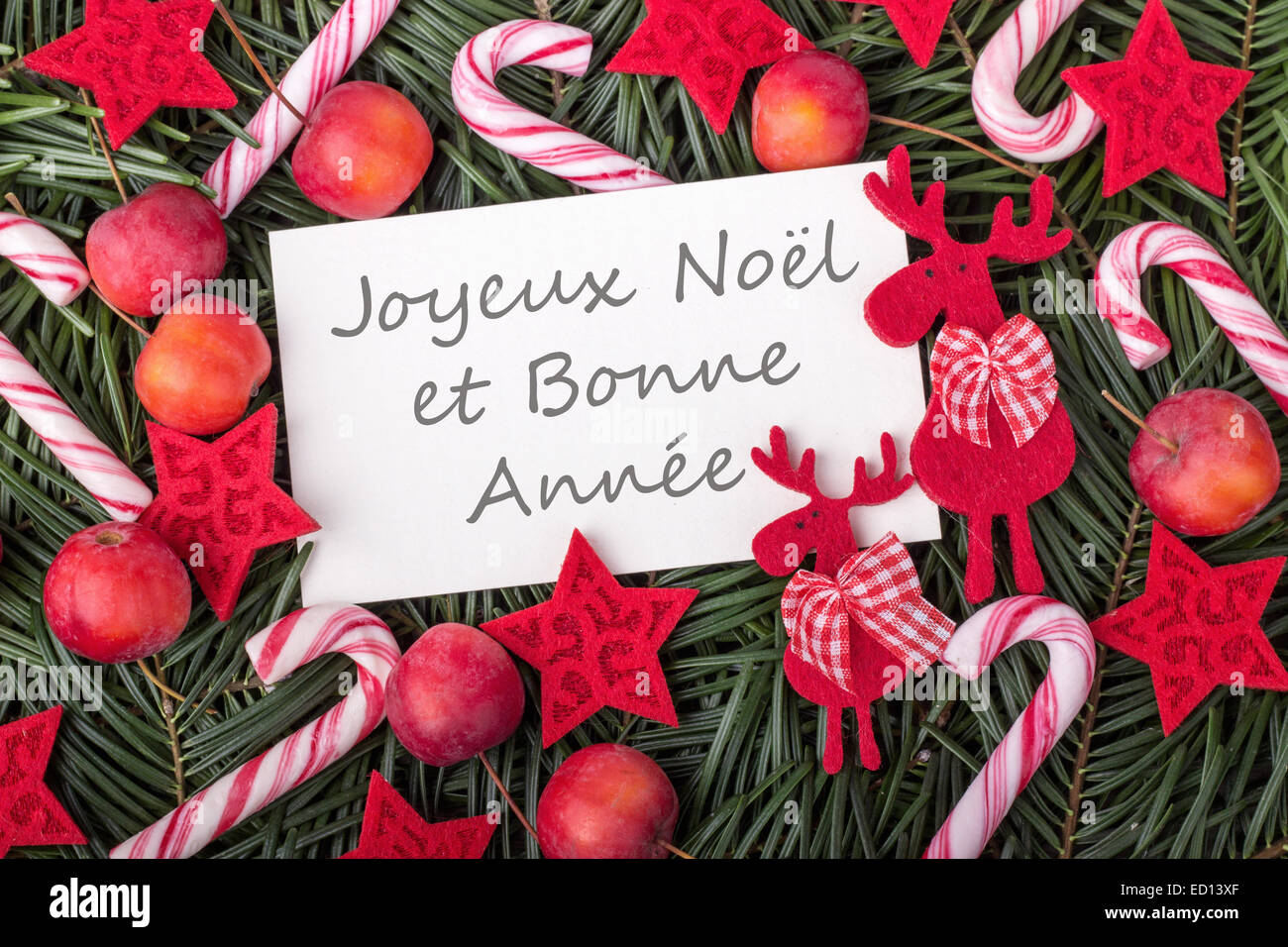 french christmas card with pine green candy canes apples and text merry christmas and a happy new year